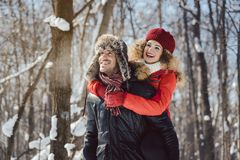 Man carrying his woman piggyback on a winter day. Man carrying his women piggyback on a winter day in a joyful manner, they have fun in this season royalty free stock photos