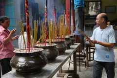 Man carrying incense sticks in Buddhist temple Royalty Free Stock Photos