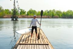 Man carrying kayak and oar after water sports at warm weather. Water fun on summer vacation. Sportive guy standing on boardwalk pier with modern paddle and white stock photography