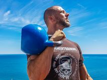 Man Carrying Kettlebell Near Body of Water Royalty Free Stock Photos