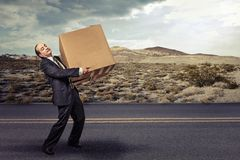 Man carrying large carton box. On a countryside road Stock Photo
