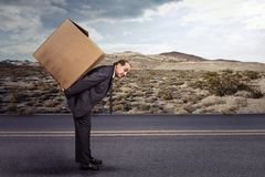 Man carrying large carton box. On his back on a remote countryside road. Delivery, shipping, moving goods concept Royalty Free Stock Images