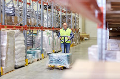 Man carrying loader with goods at warehouse Stock Image
