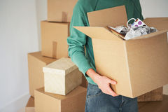 Man Carrying Open Cardboard Box. Midsection of man carrying open cardboard box in new home Stock Images