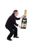 Man carrying an oversized champagne bottle Stock Images