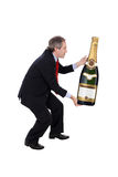 Man carrying an oversized champagne bottle Stock Photo
