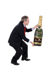 Man carrying an oversized champagne bottle Royalty Free Stock Photo