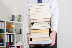 Man carrying a pile of books. At office Royalty Free Stock Photos