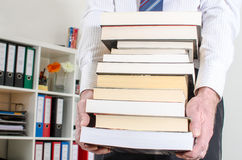Man carrying a pile of books. At office Royalty Free Stock Images