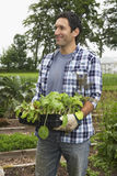 Man Carrying Plants In Field Royalty Free Stock Photo