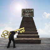 Man carrying pound symbol key toward treasure chest. Man carrying pound symbol key and walking toward the treasure chest on top of wood stairs stock image