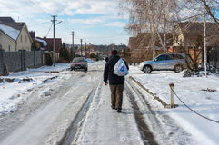 Man carrying purchases from a remote local shop walking on a snowy, slippery street. Novooleksandrivka village, Dnepropetrovsk oblast, Ukraine - January 29, 2016 Stock Photos