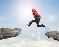 Man carrying red arrow sign jumping over two cliffs Royalty Free Stock Photo