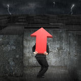 Man carrying red arrow up sign entering maze with dark Stock Image
