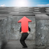 Man carrying red arrow up sign entering maze with sky Stock Images