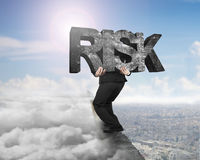 Man carrying risk concrete word on ridge with cloudscape citysca Stock Photography