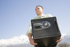 Man carrying safe near mountains Royalty Free Stock Images