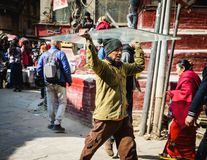 Man carrying a sheet of glass on his head, in Kathmandu, Nepal. KATHMANDU, NEPAL - CIRCA JANUARY 2017: Nepali man carrying a sheet of glass on his head in Asan Royalty Free Stock Image