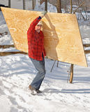 Man carrying a sheet of plywood. Through snow stock images