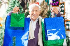 Man Carrying Shopping Bags In Christmas Store Stock Image
