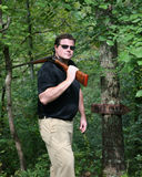 Man carrying a shotgun. In the woods with the barrel open for safety.  A DEER CAMP sign is to his right Royalty Free Stock Photo