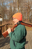 Man carrying shotgun at trap range. Man wearing safety glasses carrying a shot gun over his shoulder in early spring with bare trees in background at trap Stock Photo