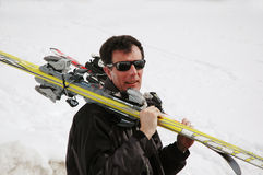 Man carrying skis. Portrait of man carrying skiis home after sking stock photo