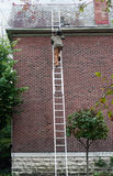 Man Carrying Slate up Ladder. Roofing contractor carrying slate up ladder to repair old slate roof Royalty Free Stock Photos