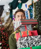 Man Carrying Stacked Christmas Gifts In Store Stock Photos