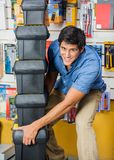 Man Carrying Stacked Toolboxes In Hardware Store Royalty Free Stock Photo