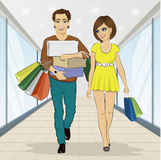 Man carrying stacks of boxes and shopping bags while his girlfriend looking at him Stock Photo