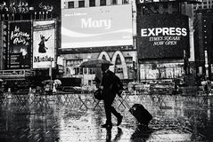 New York City - Times Square. A man carrying a suitcase during a rainy night in Time Square New York