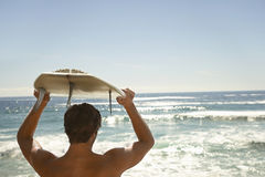 Man Carrying Surfboard Above Head By Ocean. Rear view of young man carrying surfboard above head by ocean Stock Images