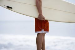 Man Carrying Surfboard On Beach. Midsection of young man carrying surfboard on beach Stock Photo