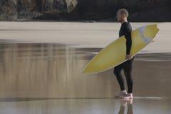 Man Carrying Surfboard On Beach. Full length side view of man carrying surfboard on beach Stock Photos