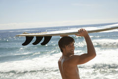 Man Carrying Surfboard By Ocean Royalty Free Stock Photography