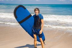 Man carrying surfboard over his head. Close up of handsome guy with surfboard on head at beach. Portrait of man carrying royalty free stock photos