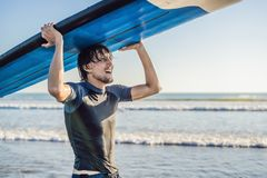 Man carrying surfboard over his head. Close up of handsome guy with surfboard on head at beach. Portrait of man carrying stock photo