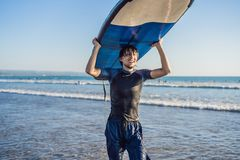 Man carrying surfboard over his head. Close up of handsome guy with surfboard on head at beach. Portrait of man carrying stock photos