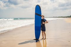 Man carrying surfboard over his head. Close up of handsome guy w. Ith surfboard on head at beach. Portrait of man carrying surfboard on hid head and smiling at stock photos