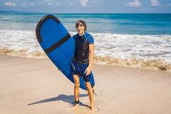 Man carrying surfboard over his head. Close up of handsome guy w. Ith surfboard on head at beach. Portrait of man carrying surfboard on hid head and smiling at stock image