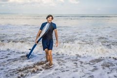 Man carrying surfboard over his head. Close up of handsome guy w. Ith surfboard on head at beach. Portrait of man carrying surfboard on hid head and smiling at royalty free stock images