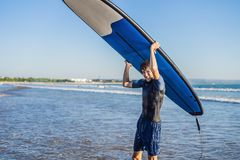 Man carrying surfboard over his head. Close up of handsome guy w. Ith surfboard on head at beach. Portrait of man carrying surfboard on hid head and smiling at Royalty Free Stock Photos