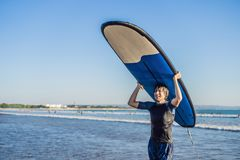 Man carrying surfboard over his head. Close up of handsome guy w. Ith surfboard on head at beach. Portrait of man carrying surfboard on hid head and smiling at Royalty Free Stock Photo