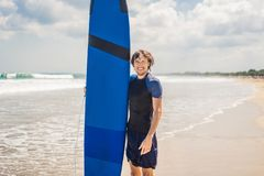 Man carrying surfboard over his head. Close up of handsome guy w. Ith surfboard on head at beach. Portrait of man carrying surfboard on hid head and smiling at royalty free stock photography