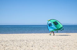 Man Carrying a Tent on the Beach Royalty Free Stock Photos
