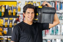 Man Carrying Toolbox On Shoulder In Hardware Store. Portrait of confident young man carrying toolbox on shoulder in hardware store Stock Photography