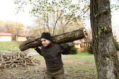 Man carrying tree trunk on his shoulders for heating in winter. Royalty Free Stock Images