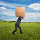 Man carrying two heavy boxes at outdoor Royalty Free Stock Images