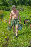 Man carrying water 2. The gardener is carrying a water with buckets Stock Photography